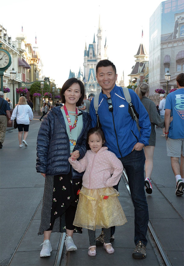 Tan and his family in front of the castle in Disney's Magic Kingdom.